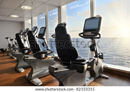 elliptical cross trainer in a row in a gym on a cruise liner with a view to the ocean - stock photo