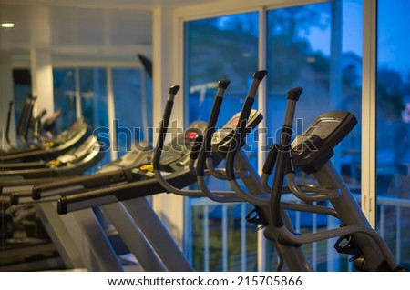 Elliptical cross trainers in a fitness gym at evening - stock photo