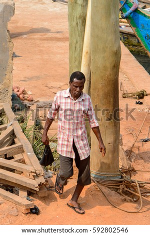 ELMINA, GHANA -JAN 18, 2017: Unidentified  Ghanaian man in plaid shirt walks in Elmina . People of Ghana suffer  poverty due to the bad economy.