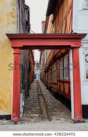 ELSINORE, DENMARK - APRIL 30, 2016: Entrance port to a narrow alley paved with cobblestones, with an open gutter, in the medieval quarter of Elsinore. - stock photo
