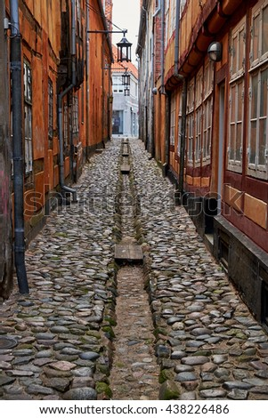 ELSINORE, DENMARK - APRIL 30, 2016: Very narrow alley paved with cobblestones, with an open gutter, in the medieval quarter of Elsinore. - stock photo