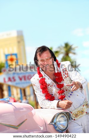Elvis impersonator and Las Vegas on the strip pointing looking at camera in front of Welcome to Fabulous Las Vegas sign and car.