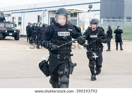 ELWOOD, ILLINOIS - OCTOBER 1, 2012: Riot police at the Walmart distribution center run up to striking warehouse workers and supporters as they rally for better wages and working conditions. - stock photo