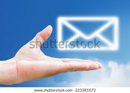 Email icon on hand and mail sybol icon clouds on blue sky - stock photo