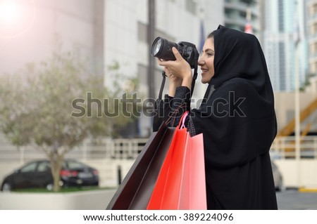 Emarati Arab woman coming out of shopping and taking photo with her camera in Dubai, United Arab Emirates. - stock photo