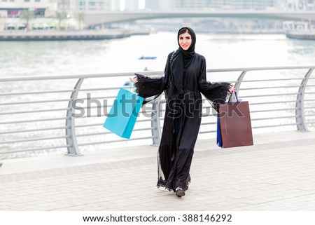 Emarati Arab woman coming out of shopping with bags in her hand in Dubai, United Arab Emirates. - stock photo