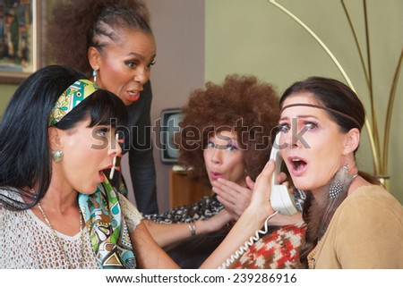 Embarrassed group of female friends listening to telephone - stock photo