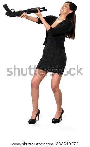 Embarrassed Hispanic young woman with long dark brown hair in casual outfit holding shotgun - Isolated - stock photo