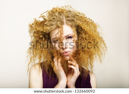 Embarrassment. Shaggy Red-Haired Curly woman grimacing. Play the Ape - stock photo