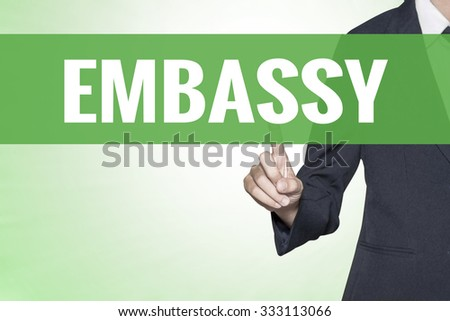 Embassy word on green virtual screen touching by business woman - stock photo