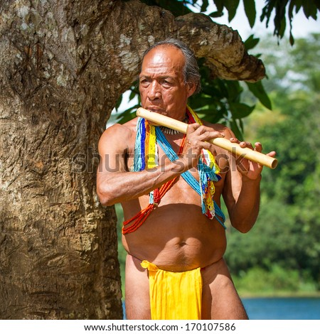 EMBERA VILLAGE, PANAMA, JANUARY 9, 2012: Unidentified native Indian man plays a flute in Panama, Jan 9, 2012. Indian reservation is the way to conserve native culture, languange, traditions