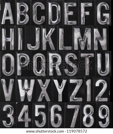 Embossed and sanded metal type on black - stock photo