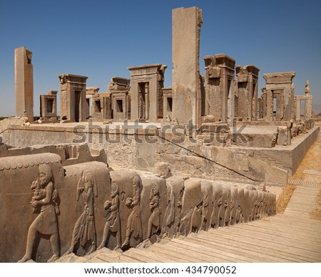 Embossed bas relief carvings of servants bringing gifts to the king on the sidewall of stairs in front of Tachara Palace or Palace of Darius in Persepolis of Shiraz. - stock photo
