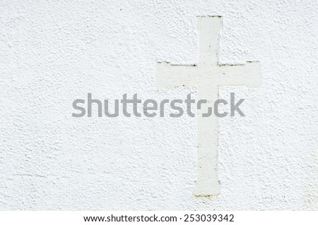 Embossed christian cross on church stone wall in white. Cross to the right in picture and place for text to the left. - stock photo