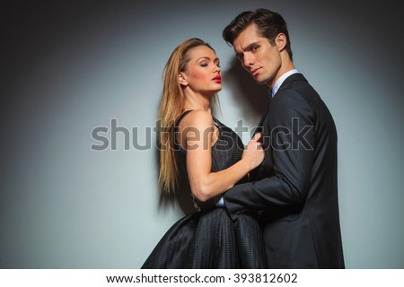 embraced couple in black posing in gray studio background. man has his hands on her waist while looking at the camera. woman pulls his jacket while looking down.  - stock photo