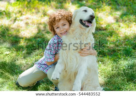 Embracement with favorite pet from one little boy with an awesome curly hair of red color. Beautiful golden retriever with soft fur.