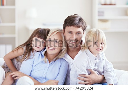Embracing a happy family with children at home - stock photo