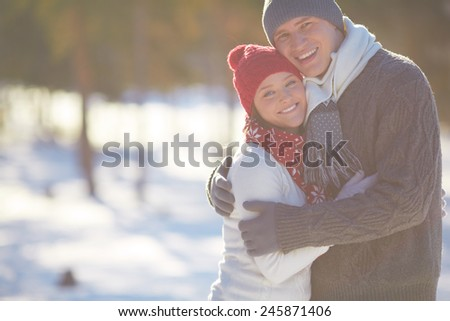 Embracing couple in casual winterwear looking at camera outdoors - stock photo