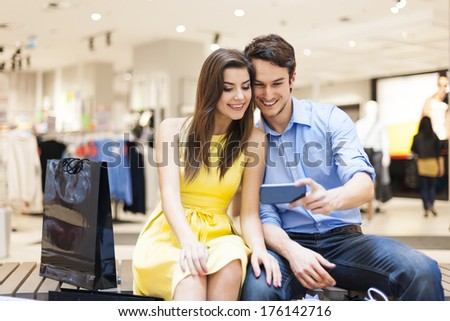 Embracing couple sitting in shopping mall and looking on mobile phone - stock photo