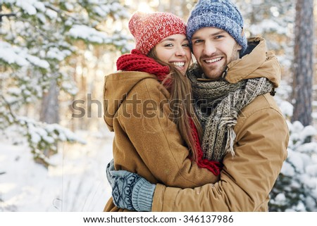 Embracing dates in winterwear looking at camera in natural environment - stock photo