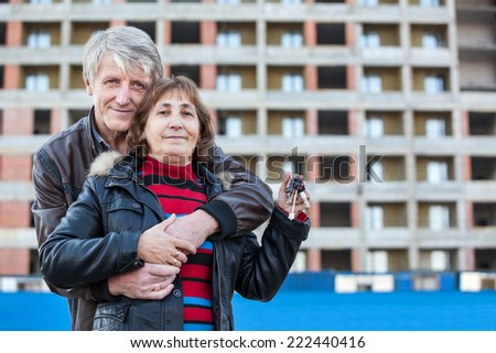 Embracing loving mature couple with house key in hand, copyspace - stock photo