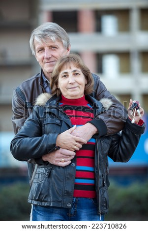 Embracing loving senior couple with house key in hand - stock photo
