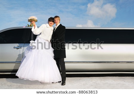 embracing smiling groom and bride with bouquet of roses stand near wedding limousine at winter outdoors - stock photo