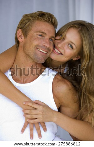 Embracing young couple. The young man is carrying the young girl on his back. - stock photo