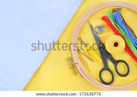 Embroidery and cross stitch accessories on yellow and light blue linen fabric. Embroidery hoop, scissors, thread, needles, thimble. Copy space. - stock photo