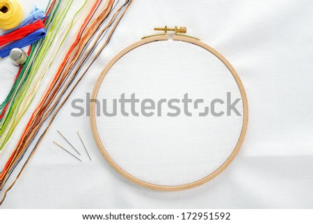 Embroidery set. White linen fabric, embroidery hoop, colorful threads and needls. Copy space. - stock photo