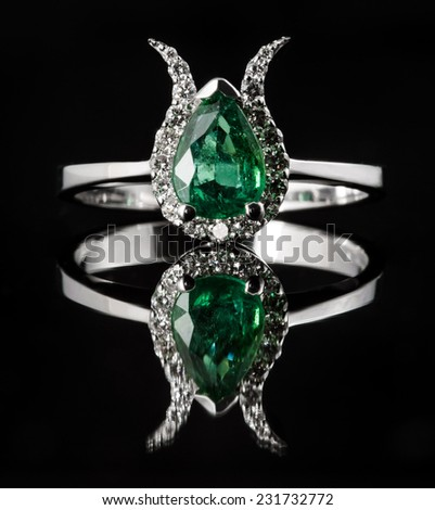 Emerald and diamond engagement ring isolated on black background with reflection - stock photo