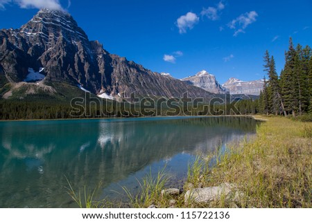 Emerald green lake with mountain peak on background - stock photo