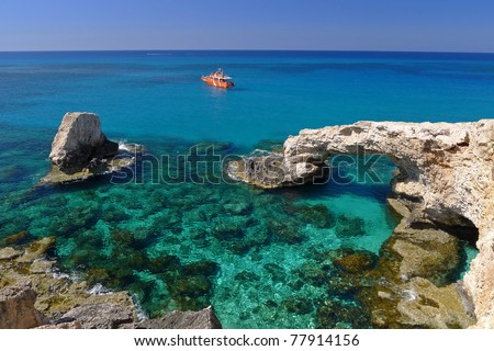 Emerald green sea water with rock arch on Cyprus island - stock photo