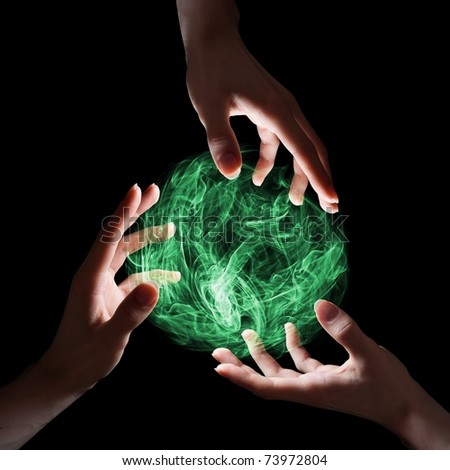 Emerald magical sphere held by three hands. - stock photo