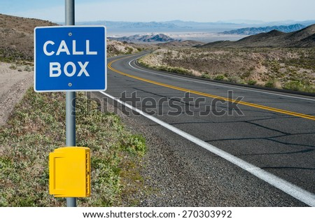 Emergency Call Box and Sign:  A sign informs motorists of telephone assistance available on a desert highway in California.