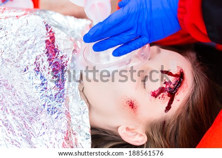 Emergency doctor and nurse or ambulance team giving oxygen to accident victim  - stock photo