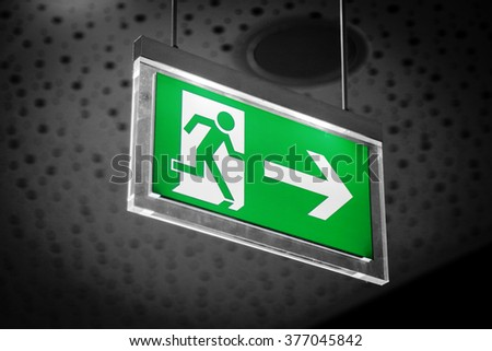 Emergency exit light sign on a gray background - stock photo