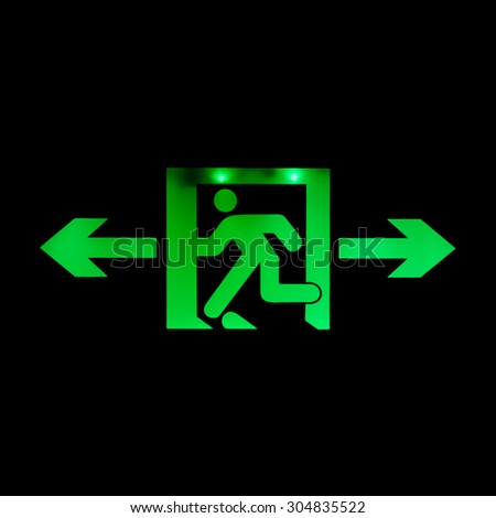 Emergency exit sign glowing in green on the dark background. - stock photo