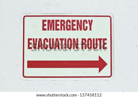 Emergency sign shows an arrow for the evacuation route. - stock photo