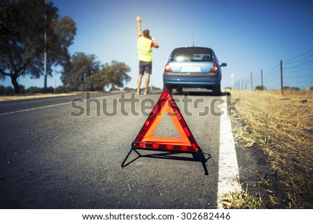 Emergency triangle on the road. Stopped car and man calling by phone in the background. - stock photo