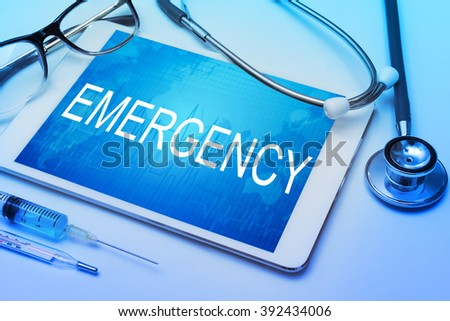 Emergency word on tablet screen with medical equipment on background - stock photo