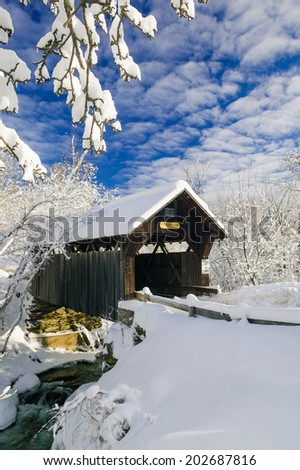 Emily's Covered Bridge blanketed in fresh snow on a sunny winter morning, Stowe, Vermont, USA - stock photo