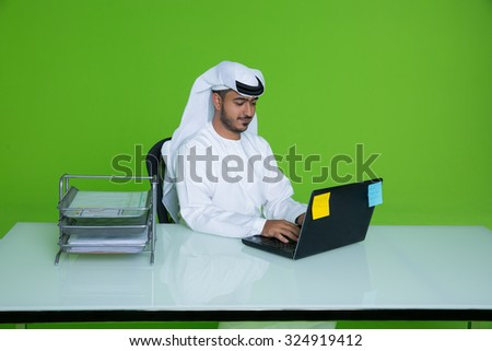 Emirati businessman using laptop - stock photo