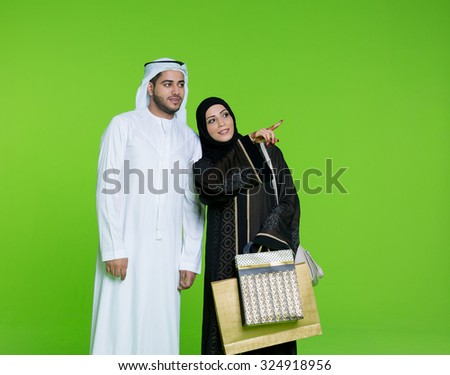 Emirati couple looking with curiosity - stock photo