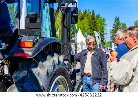 Emmaboda, Sweden - May 13, 2016: Forest and tractor (Skog och traktor) fair. Visitors standing outside a tractor having a talk.