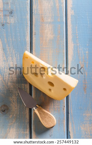 Emmental cheese piece with cheese knife - stock photo