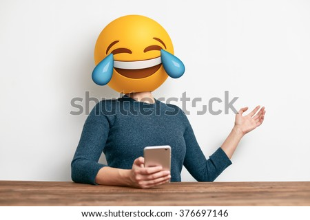 Emoji Head Woman sitting at the desk. Woman wearing tears of joy emoji masks while looking at her phone. This emoji is laughing so much that it is crying tears of joy - stock photo