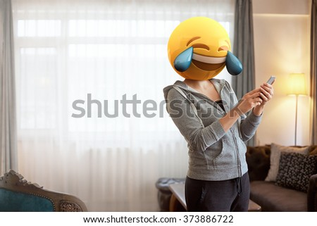 Emoji Head Woman. Woman wearing tears of joy emoji masks while looking at her phone. This emoji is laughing so much that it is crying tears of joy - stock photo