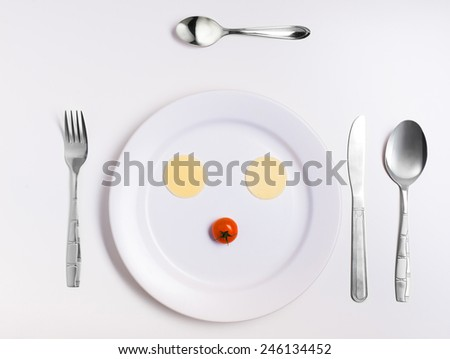 emoticon food, made from cheese, tomatoes, on a plate with cutlery
