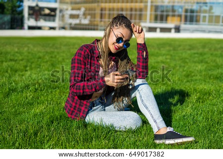 Emotiomal beautiful girl with zizi cornrows dreadlocks chatting on her smartphone sitting on the lawn. She is smiling